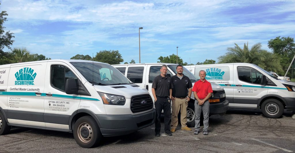 Staff members standing in front of the vans for Optima Security, Inc. in Jacksonville, FL